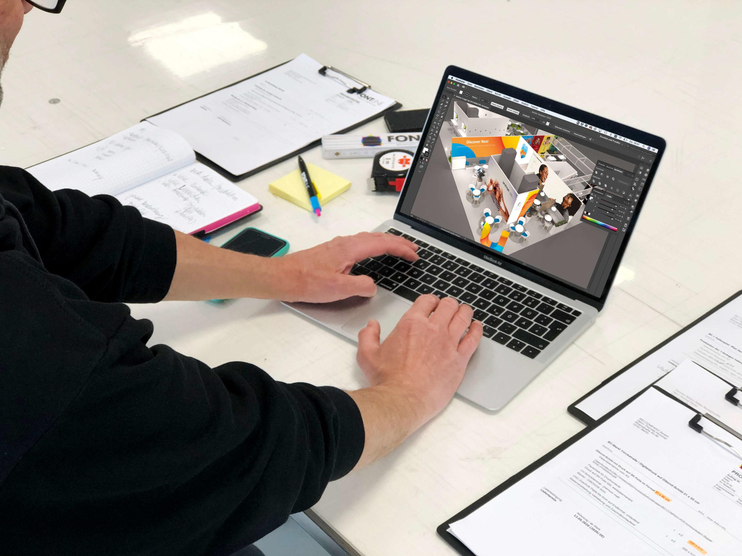 Draufsicht auf einen Laptop, der auf einem Arbeitstisch steht umgeben von Notiz- und Auftragszetteln.