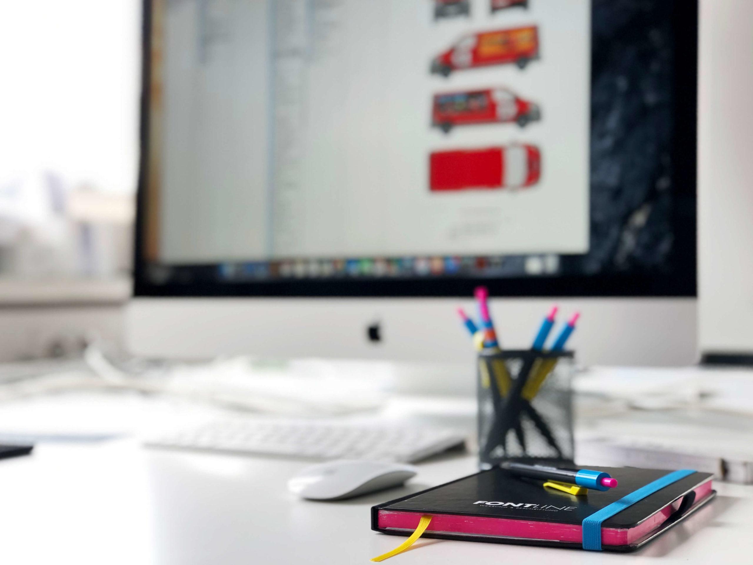 Nahansicht eines Schreibtisches mit Arbeitsmaterialien und Bildschirm.