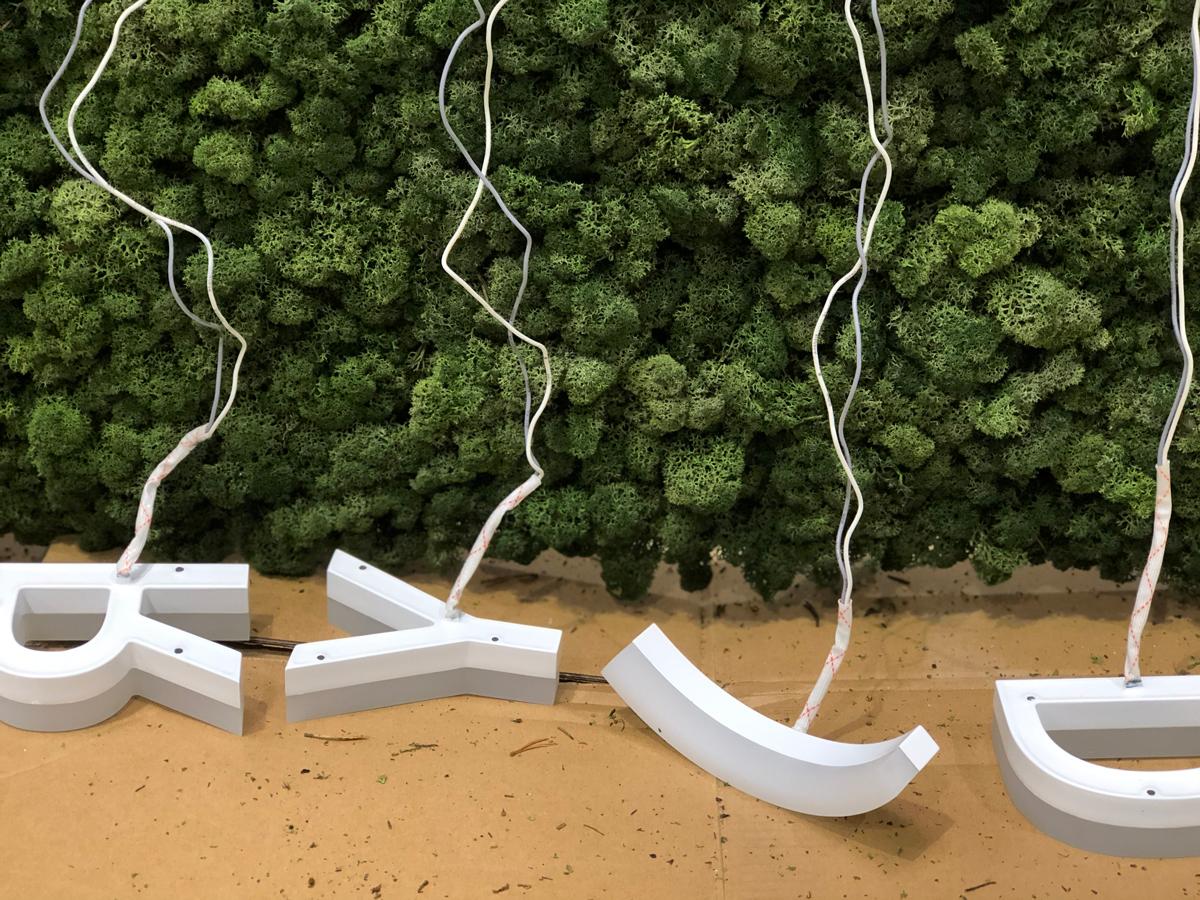 Weiß leuchtende, ausgefräste Acryl-Buchstaben montiert auf einer Moosrückwand.