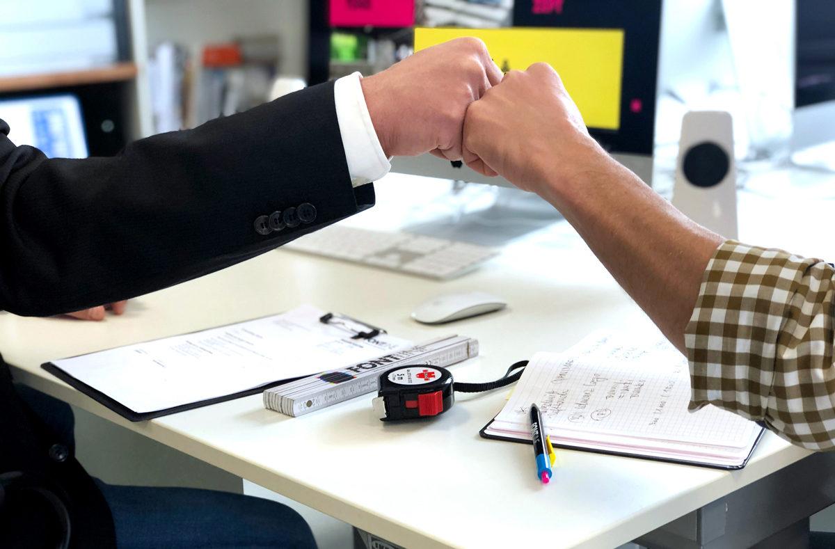 Wir sind ein Team. Zwei Fäuste über einem Schreibtisch vor einem Computerbildschirm treffen sich.