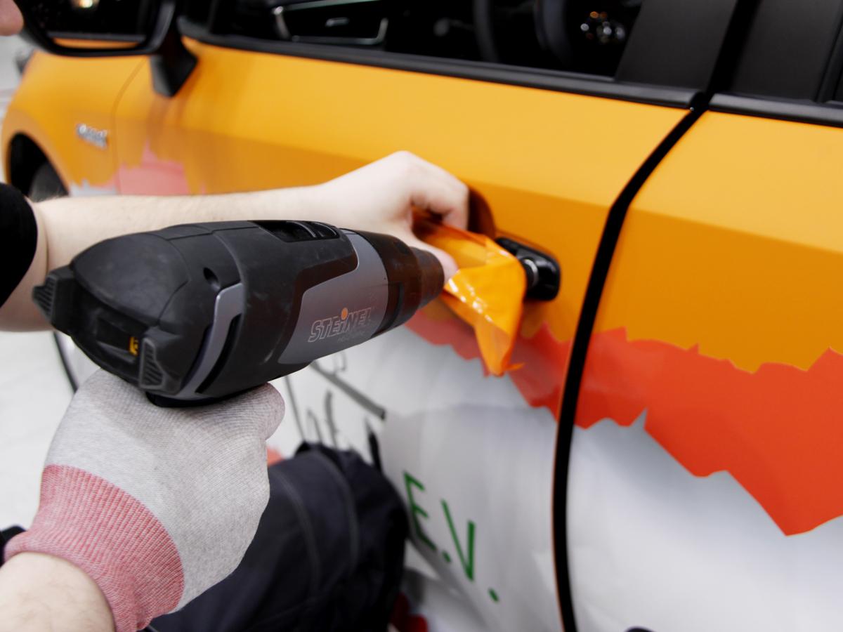 Ein Werbetechniker beim erhitzen einer Folie.
